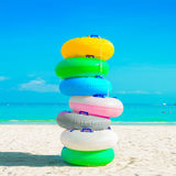 Stack of colorful rubber rings (or swim rings) on white sand beach. Summer holiday concept Royalty Free Stock Photo