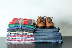 Stack of colorful shirts, jeans and shoes on table against light background stock photo