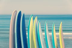 Stack of colorful surfboads on ocean background with waves. Retro vintage filter Royalty Free Stock Photo