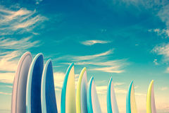 Stack of colorful surfboards on blue sky background with copy space, retro vintage filter stock image