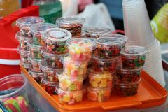 Stack of colorful sweetmeat in the plastic cup for sale. In the market royalty free stock image