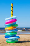 Stack of colorful swimming rings on sea beach Royalty Free Stock Photography
