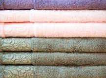 Stack of colorful terry towels folded. Shop Home. Numerous towels stacked and folded on the shelves of a store.  Royalty Free Stock Photography