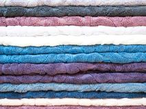 Stack of colorful terry towels folded. Shop Home. Numerous towels stacked and folded on the shelves of a store.  Royalty Free Stock Photo