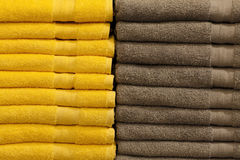 Stack of colorful terry towels folded. Shop Home. Two stacks of yellow and brown towels stacked and folded on the shelves of a store. Interior home store Royalty Free Stock Photography