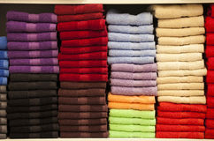 Stack of colorful terry towels folded. Shop Home. Numerous towels stacked and folded on the shelves of a store. Purple, black, red, brown, blue, lilac, orange Royalty Free Stock Photography