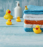 Stack of colorful towels and bath duck on the table Stock Image