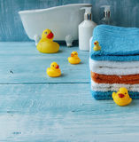 Stack of colorful towels and bath duck on the table Royalty Free Stock Photography