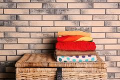 Stack of colorful winter clothes on wicker chest near brick wall. Space for text stock photography