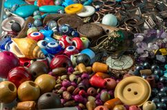 Stack of colorful wooden beads, buttons, pearls, devil eyes, and metal items. Photograph of a stack of colorful wooden beads, buttons, pearls, devil eyes, and royalty free stock photo
