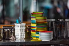 Stack of colourful dishes on stainless steel table. Stack of colourful clean dishes on stainless steel table. Urban outdoor cafe background Stock Photography