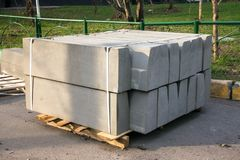 Stack of concrete road curbs in a yard for the overhaul of a sidewalk, organised by municipal public utility service. Stack of concrete road curbs in a yard for stock photography