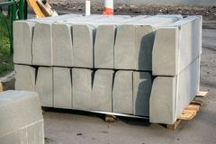 Stack of concrete road curbs in a yard for the overhaul of a sidewalk, organised by municipal public utility service. Stack of concrete road curbs in a yard for royalty free stock photography