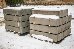 Stack of concrete road curbs in a yard for the overhaul of a sidewalk, organised by municipal public utility service. Winter 2018 stock images