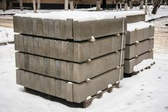 Stack of concrete road curbs in a yard for the overhaul of a sidewalk, organised by municipal public utility service. Winter 2018 royalty free stock image