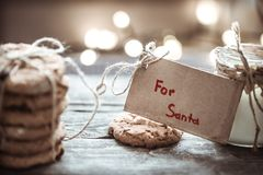 Milk and cookies for Santa. A stack of cookies and glass of milk for Santa on wooden background, concept Christmas and holiday Royalty Free Stock Photo