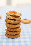 Stack of cookies with orange jam centers. On a blue gingham check tablecloth Royalty Free Stock Image