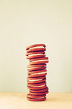 Stack of cookies over wooden table next to cup of coffee. image is retro style filtered Stock Photography