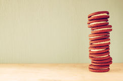 Stack of cookies over wooden table next to cup of coffee. image is retro style filtered Royalty Free Stock Photo