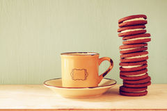 Stack of cookies over wooden table next to cup of coffee. image is retro style filtered Stock Photo