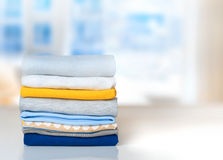 Stack cotton folded clothes on table indoors empty space. Cotton stack of colorful folded clothes on white table indoors empty space background.Household Royalty Free Stock Photos