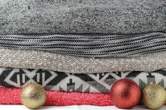 Stack of cozy colorful sweaters with festive glitter christmas d. Ecoration ball royalty free stock photo