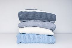 Stack of cozy comfortable homely clean washed knitted sweaters in pastel colors, laundry and washing clothes concept.  stock images