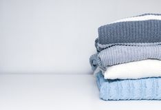 Stack of cozy comfortable homely clean washed knitted sweaters in pastel colors, laundry and washing clothes concept with copy. Space stock images