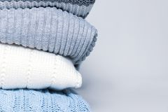 Stack of cozy comfortable homely clean washed knitted sweaters in pastel colors, laundry and washing clothes concept with copy. Space stock photos