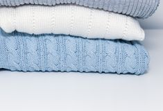 Stack of cozy comfortable homely clean washed knitted sweaters in pastel colors, laundry and washing clothes concept with copy. Space stock image