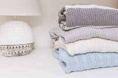 Stack of cozy comfortable homely knitted sweaters in pastel colors, cosy homelike clothes concept with copy space.  stock image