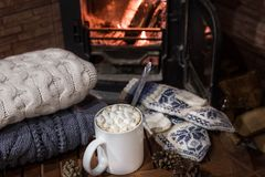 Stack of cozy knitted sweaters, handmade mittens and cup of coffee with marsh mallows on old wooden table, near burning. Fireplace Royalty Free Stock Image