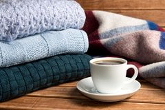 Stack of cozy knitted warm sweater and a blanket. Sweaters in retro Style and a Cup of coffee. The concept of warmth and comfort Stock Photography