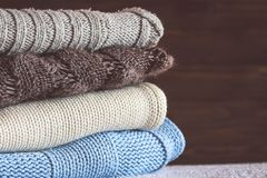 Stack of cozy knitted warm sweater ,home background . White Swea. Ters in blue and brown retro Style.Toning Royalty Free Stock Photography