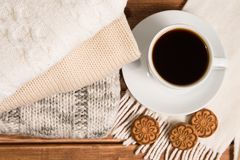 Stack of cozy knitted warm sweater , wooden background . Sweater. S in retro Style and a Cup of coffee. The concept of warmth and comfort Stock Photos