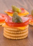 Stack of crackers, top one loaded with cheese, tomato, pepperoni and pickle Royalty Free Stock Images