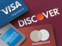 Stack of credit cards showing the logo from major credit networks: Visa, Discover, American Express, and Mastercard stock images