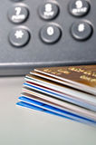 Stack of Credit cards and telephone in background Stock Photos