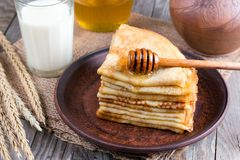 Stack of crepes or pancakes for Maslenitsa. Stack of classic Russian thin pancakes bliny or crepes with honey on a plate. Traditional for the Russian pancake royalty free stock photography