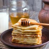 Stack of crepes or pancakes for Maslenitsa. Stack of classic Russian thin pancakes bliny or crepes with honey on a plate. Traditional for the Russian pancake stock photos