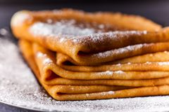 Stack of crepes with powdered sugar on dark background. Pancakes for breakfast Stock Images