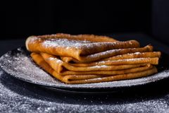 Stack of crepes with powdered sugar on dark background. stock photography