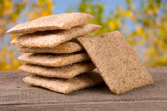 Stack of crisp bread on a wooden table with blurred garden background Royalty Free Stock Images