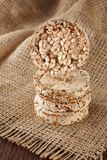 Stack of crispbreads on homespun napkin over dark light wooden table, close-up, selective focus. Stack of diet crispbreads on homespun napkin over light wooden Royalty Free Stock Photos