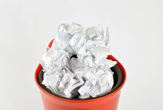 Crumpled white papers in a plastic trash can  on white royalty free stock photos