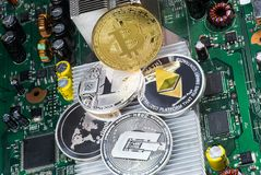 Stack of cryptocurrencies: bitcoin, ethereum, litecoin, dash, and ripple coin together. The background is a computer circuit Board. With chips, macro shot stock photos