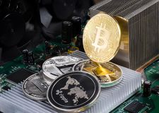 Stack of cryptocurrencies: bitcoin, ethereum, litecoin, dash, and ripple coin together. The background is a computer circuit Board with chips royalty free stock photo