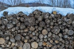 Stack of cut wood under the snow stock photos