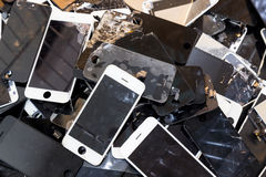 Stack of damaged smart phone body and cracked LCD screen royalty free stock image