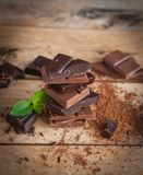 Stack of dark and milk chocolate with fresh mint on wooden background stock photography